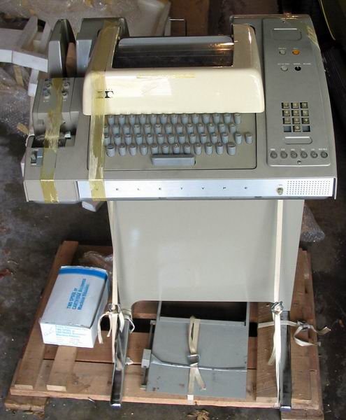 The full ASR33 Teletype on the pallet showing the unit, stand, paper holder and a box of ribbons