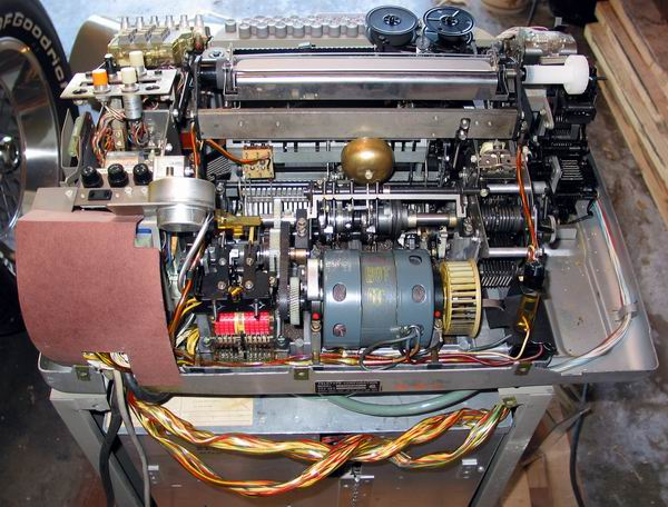 A rear view of the ASR33 Teletype with the cover off showing the motor and inner workings